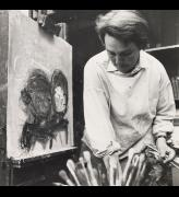 Audrey Walker. Joan Eardley at easel, looking downwards and holding paintbrushes. Photograph: John McKenzie. © Jane Walker.
