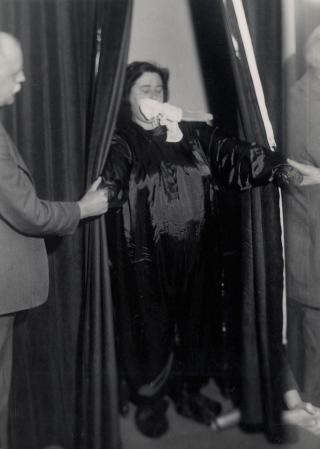 Helen Duncan emerging from curtains with 'ectoplasm' – her hands holding those of others