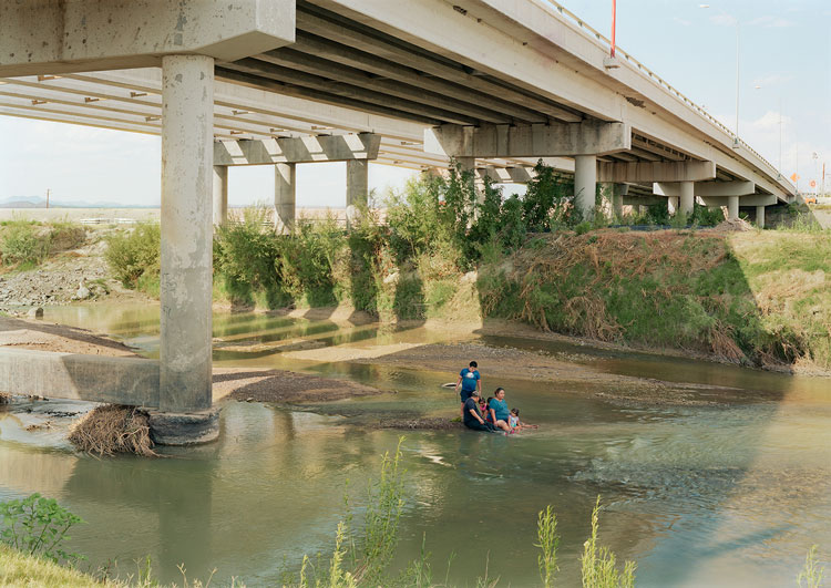 An-My Lê. Fragment IV: Family under the Presidio-Ojinaga-International Bridge, Texas/Mexico Border, from The Silent General, 2019. Pigment print, 56 1/2 x 40 in (143.5 x 101.6 cm). © An-My Lê. Courtesy the artist and Marian Goodman Gallery New York, Paris and London.