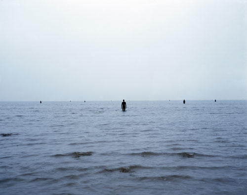 Antony Gormley. <em>Another Place</em>, 1997. Cast iron, 189 x 53 x 29 cm (100 elements). Installation view, Cuxhaven, Germany. © Antony Gormley. Photograph by Helmut Kunde.