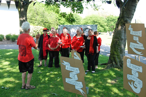 <p>The Strawberry Thieves Choir, with placards, banner and bunting by Rachael House, 2012.