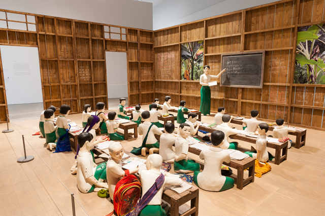 NGE Lay. The sick classroom, 2013. 27 wooden sculptures, timber walls, eight desks, 26 student accessories, one table, one chair; 15 photographs. Installation view, The 8th Asia Pacific Triennial of Contemporary Art, 2015. Collection: Queensland Art Gallery.
