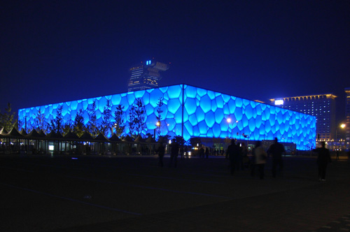 Night view of the National Aquatics Centre from the Olympic Green axis. The colour of the ETFE pillow changes to a luminous deep blue colour when illuminated from within.