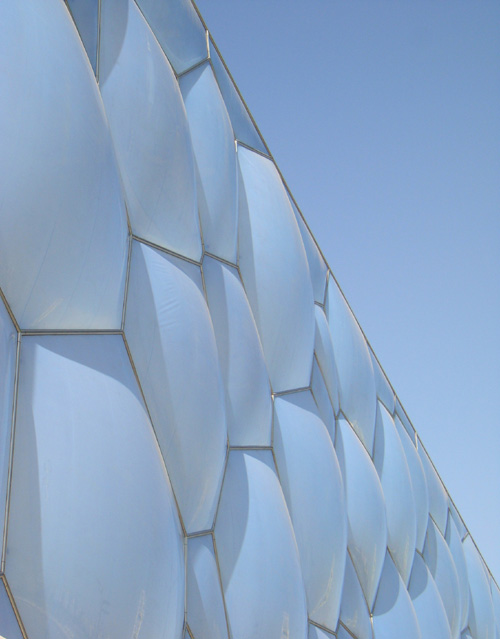The façade of the Water Cube adopting a pastel blue hue.