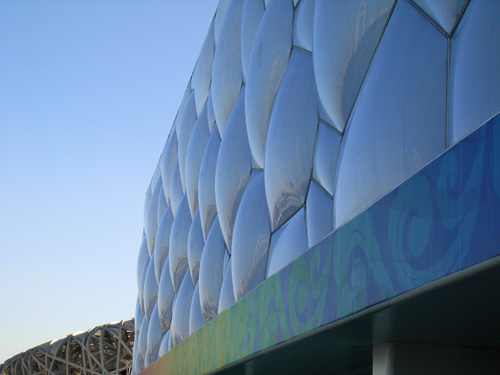 The soft, bulging ETFE pillows of the Water Cube in contrast with the hard metallic structures of the Bird Nest.