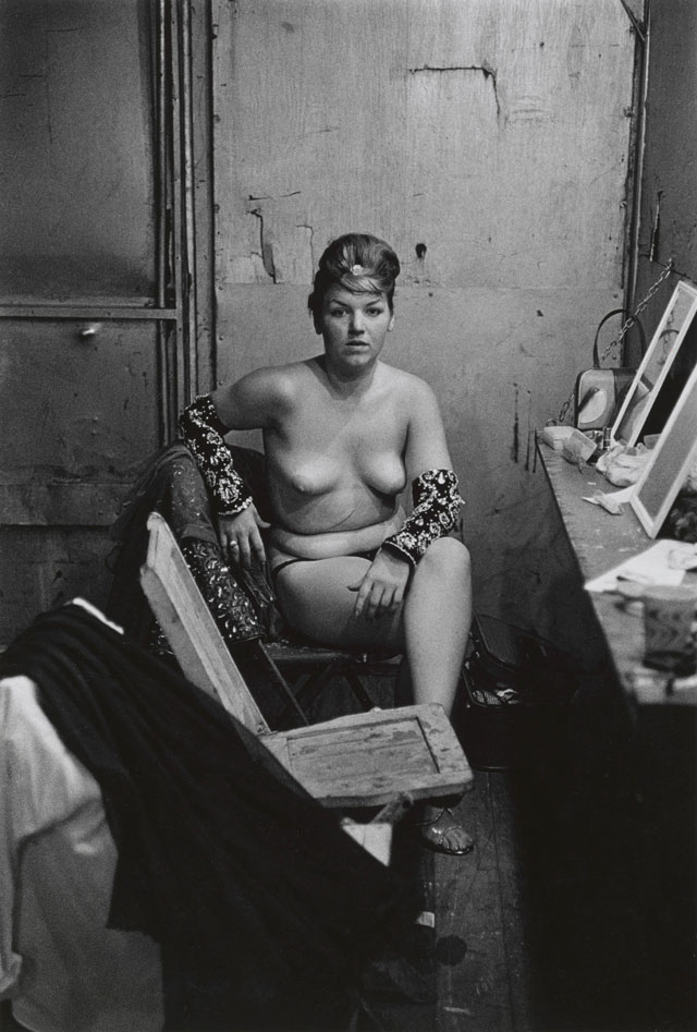 Diane Arbus. Stripper with bare breasts sitting in her dressing room, Atlantic City, N.J. 1961. © The Estate of Diane Arbus, LLC. All Rights Reserved.
