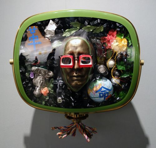 Nam June Paik. Self-Portrait, 1989. 1950s Philco Predicta TV cabinet containing bronze mask of the artist, videotape, antigue TV tubes, circuit board. eggs, painted globe, watch, suspenders, pewter Buddha, magnet, painted toy piano, I-Ching page, silk flower, 1 pair of eye glasses. Edition of 12. 24 x 27 x 16 in. Carl Solway Gallery.