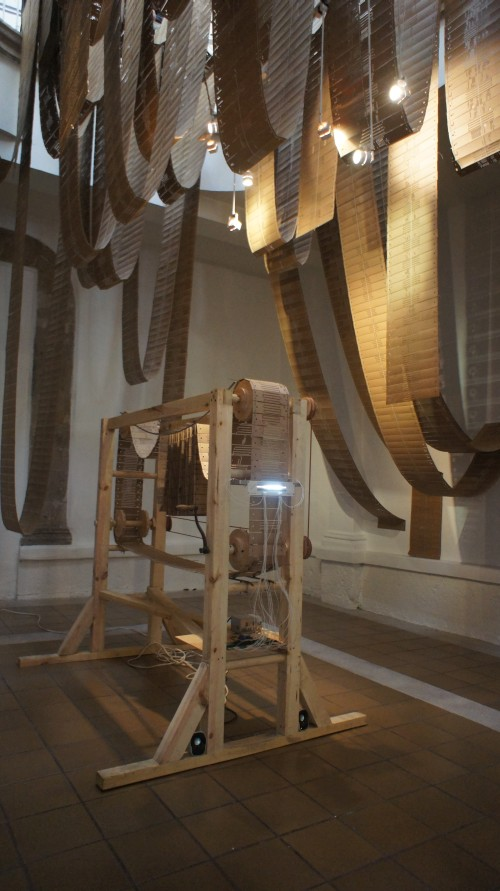 Tania Candiani. Telar/Máquina, 2012 (3). Punched cards, wooden mechanism, optical tone generator, speakers, drawings, single channel video and embroidered strips. 2.40 x 2.00 x 1.10 m. Courtesy of the artist and Instituto de Visión.