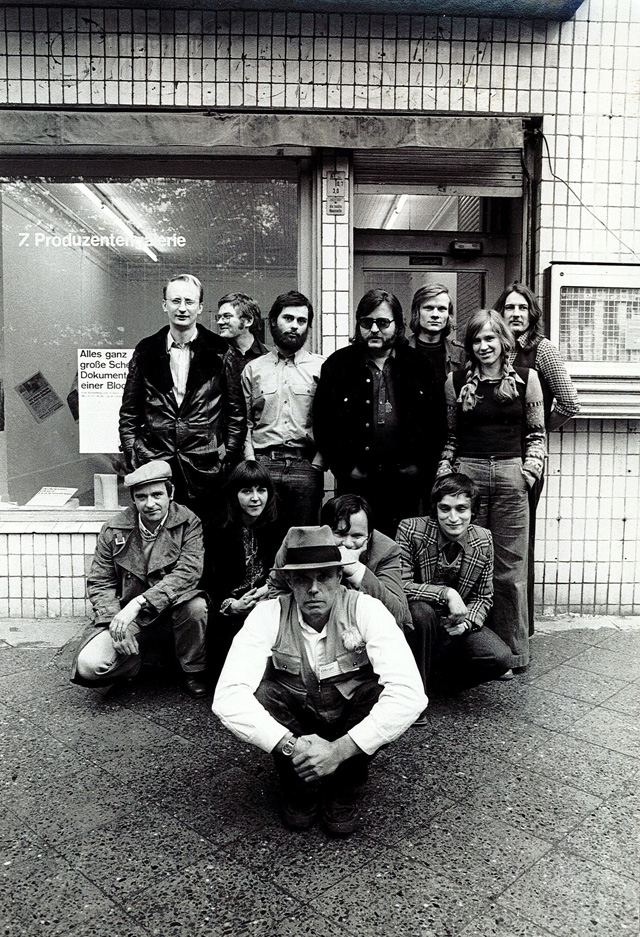 Exhibition curators and artists (back row, left to right: Klaus Staeck, Dieter Hacker, Gerhard Steidl, Christos Joachimedes, Video Cameraman, Siegrid Hacker, Martin Scutt. Front row left to right: KP Brehmer, Caroline Tisdall, Joseph Beuys, Michael Ruetz, Norman Rosenthal), taken in front of Dieter Hacker's Produktiongalerie after the Colloquium, Berlin, 1974.