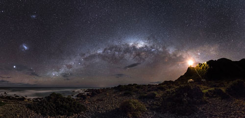EARTH AND SPACE. Winner and Overall Winner: Mark Gee (Australia), Guiding Light to the Stars. The skies of the Southern Hemisphere offer a rich variety of astronomical highlights. The central regions of the Milky Way Galaxy, 26,000 light years away, appear as a tangle of dust and stars in the central part of the image. Two even more distant objects are visible as smudges of light in the upper left of the picture. These are the Magellanic Clouds, two small satellite galaxies in orbit around the Milky Way. © Mark Gee.