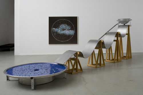 Alice Aycock. Some Night Action, 1993. Aluminum, wood, marbles, motorized parts, an undulating ramp down which marbles flow into a spinning star system; 6 h x 17 l x 5 w ft. Clear glass marbles are ejected from a pipe into a bowl and flow down an undulating ramp into a spinning circular dish with slots representing the constellations. The marbles remain in their respective places until they are knocked out of position by other shooting marbles. The marbles fall into a center void, only to be recycled again. Photograph: Tim Lee