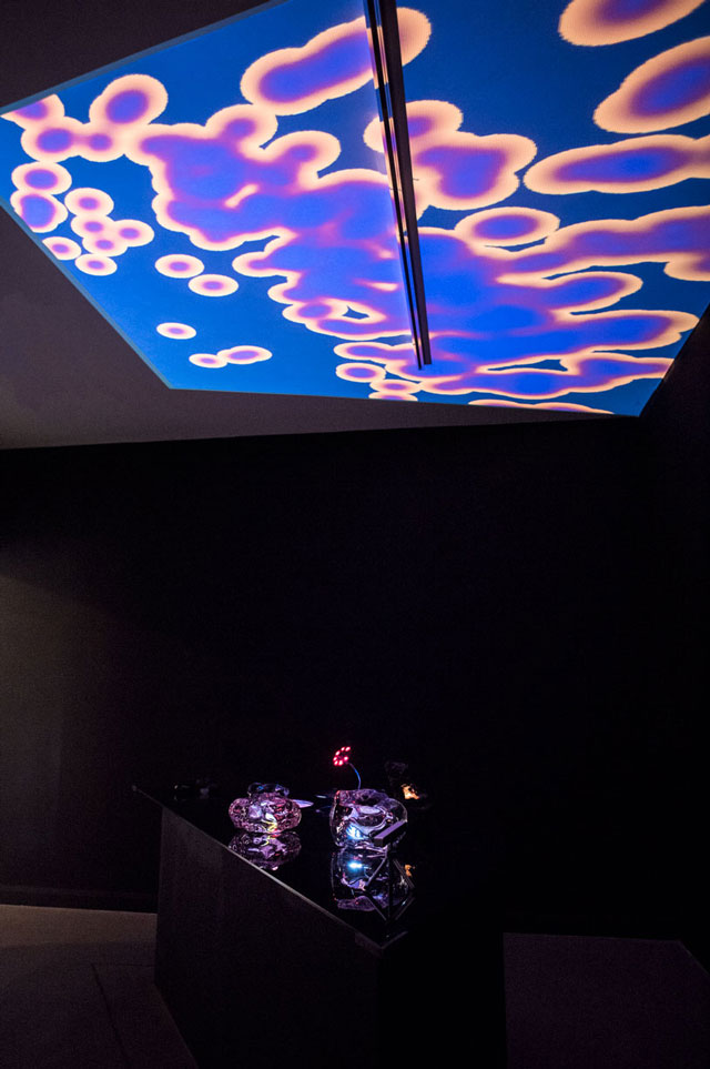 Katriona Beales. Working Table IV, 2017. Trapezoid table with glass top 240 x 800 x 77 cm and embedded flatscreen. Table top: assorted sculptures including solid glass with embedded Raspberry Pi screen and small fountain. Dimensions variable. Flatscreen: Organic control, 2017, moving image with archive footage from the B.F. Skinner Foundation duration: 06:11. Photograph: Pau Ros.