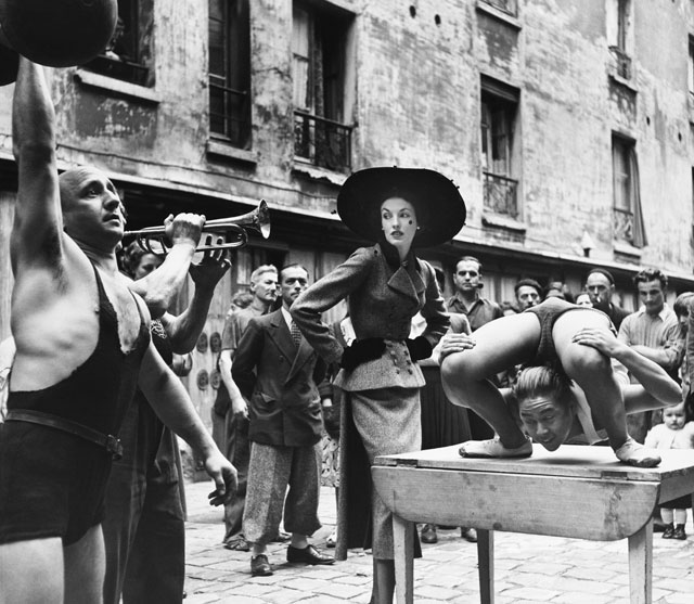 Elise Daniels with street performers, suit by Balenciaga, Le Marais, Paris, 1948. Photograph by Richard Avedon © The Richard Avedon Foundation.
