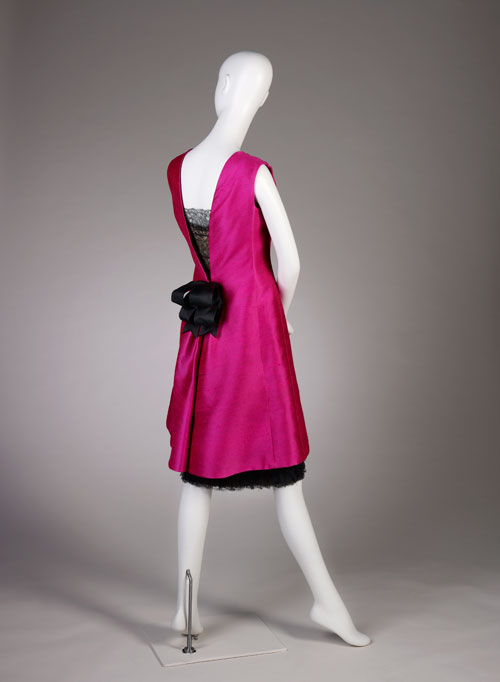 Cristobal Balenciaga. Cocktail dress of fuchsia silk shantung and black lace with black silk satin ribbons, summer 1966. Fine Arts Museums of San Francisco, the Eleanor Christensen de Guigne Collection (Mrs Christian de Guigne III), gift of Ronna and Eric Hoffman. Photo by Joe McDonald/Fine Arts Museums of San Francisco.