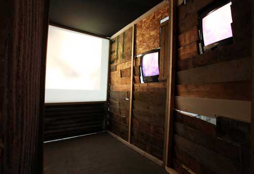 <p>Giorgio Bruni.<em> And What? (inner view), </em>2010. DVD loop, TVs, projection, wood, corrugated iron, dimensions variable. © the artist.