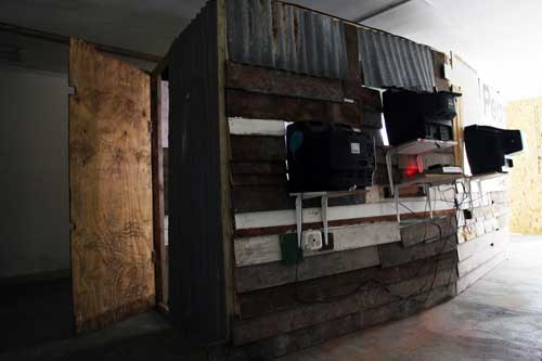 Giorgio Bruni. And What? (rear view), 2010. DVD loop, TVs, projection, wood, corrugated iron, dimensions variable. © the artist.