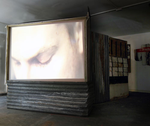 Giorgio Bruni. And What? (outer screen view), </em>2010. DVD loop, TVs, projection, wood, corrugated iron, dimensions variable. © the artist.