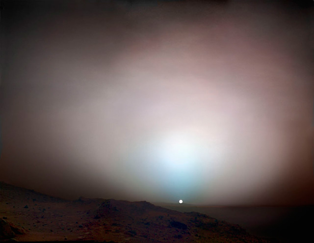 Sunset on Mars. Sunset colours on Mars in far cooler tones than those typically seen on Earth. The central blue glow is caused by sunlight scattering in the Martian atmosphere, the same phenomenon that makes Earth's sky blue. Dust suspended in the atmosphere gives the rest of the sky a copper colour. Composite photograph. Spirit Rover, 19 May 2005. NASA/JPL/Michael Benson, Kinetikon Pictures. Courtesy of Flowers Gallery.