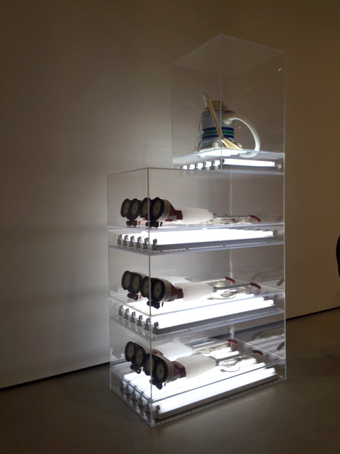 Jeff Koons. New Hoover Deluxe Shampoo Polishers, New Shelton Wet/Dry 5-Gallon Displaced Quadradecker, 1981-87. Six shampoo polishers, vacuum cleaner, acrylic and flourescent lights. Photograph: Jill Spalding.