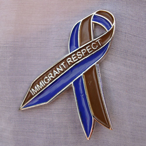 Tania Bruguera. Awareness Ribbon for Immigrant Respect Campaign, 2011.  Awareness campaign. Metal pins, community meetings, letters sent to elected officials, media. Photograph: Camilo Godoy Courtesy of Immigrant Movement International (web).