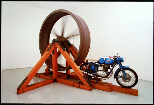 Chris Burden. The Big Wheel, 1979. Three-ton, eight-foot diameter, cast-iron flywheel powered by a 1968 Benelli 250cc motorcycle, 112 x 175 x 143 in (284.5 x 444.5 x 363.2 cm). Collection The Museum of Contemporary Art Collection, Los Angeles.