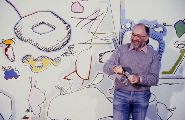 Harold Cohen holding a Turtle Robot at the San Francisco Museum of Modern Art, 1979 with a computer-generated, enlarged and hand-coloured temporary mural in the background. Courtesy Harold Cohen's archive.