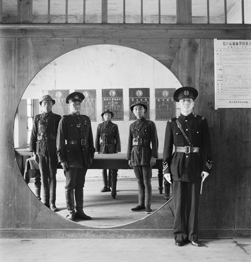 Cecil Beaton. China, 1944: The Chinese Police Force: the Assistant Chief of Police and his staff grouped in a circular doorway at headquarters in Chengtu. Part of Imperial War Museum's 'Ministry of Information Second World War Official Collection'.