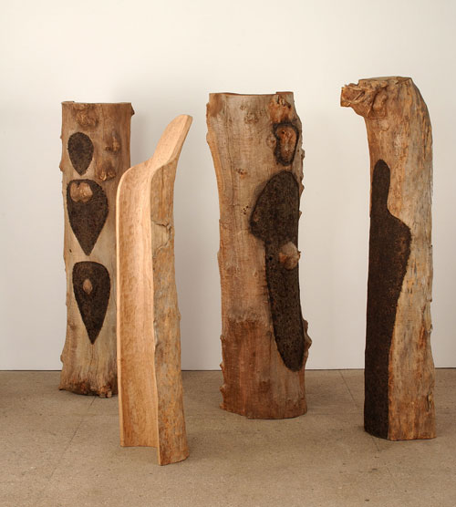 Ana Mendieta. Totem Grove 1983-85. Four semicircular tree trunks carved and burnt gunpowder. Estate Mendieta.