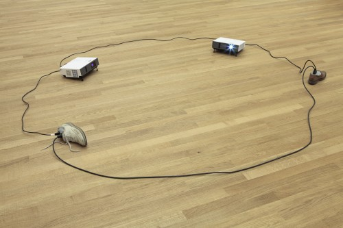 Paul Chan. Sock N Tease, 2013. Concrete, cord, shoes, and video projectors, with digital colour video, silent, 10.2 x 358.1 x 229.9 cm overall. Courtesy the artist and Greene Naftali, New York. © Paul Chan. Photograph: Tom Bisig, Basel.