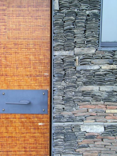 A close-up of the roof-tile wall interplay with bricks, and the steel-framed door with bamboo fascia veneer.
