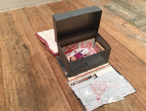 Susan Cianciolo. Mini Me, 2008-15. Steel box, coloured wood, paintings on panel, torn paper, penny, fabric, on vintage 1970s embroidery with textile by Mike Mills, 7 x 7 x 18 in (17.78 x 17.78 x 45.72 cm). Unique. Photograph: Harry Hughes.