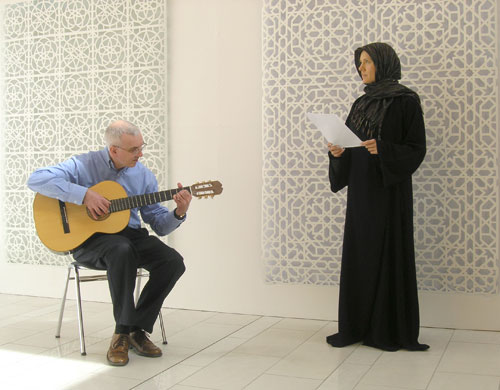 Jorge Benitez and Susan Schuld in front of Gower's Papercuts. Performance image: Jam Jar Gallery, Dubai, 15 September 2014. Photograph: Reni Gower.