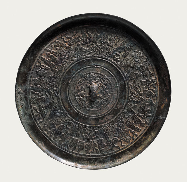 Bronze mirror with portrayals of people, Western Han (206 BCE – 8 CE), Diameter 18.6 cm (7 3/8 in), T (at edge) 0.9 cm (3/8 in), excavated in 1994 from the Marquis of Wanqu's tomb at Bojishan. Collection of the Xuzhou Museum. 人物画像铜镜,西汉,直径18.6、缘厚0.9厘米,1994年簸箕山宛朐侯墓出土,徐州博物馆藏