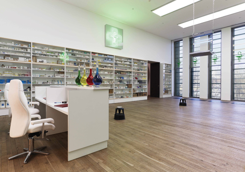 Damien Hirst. <em>Pharmacy,</em> 1992. Glass, faced particleboard, painted MDF, beech, ramin, wooden dowels, aluminium, pharmaceutical packaging, desks, office chairs, foot stools, apothecary bottles, coloured water, insect-o-cutor, medical text books, stationery, bowls, resin, honey and honey, dimensions variable. Tate. © Damien Hirst and Science Ltd. All rights reserved. DACS 2012. Photograph: Prudence Cuming Associates.
