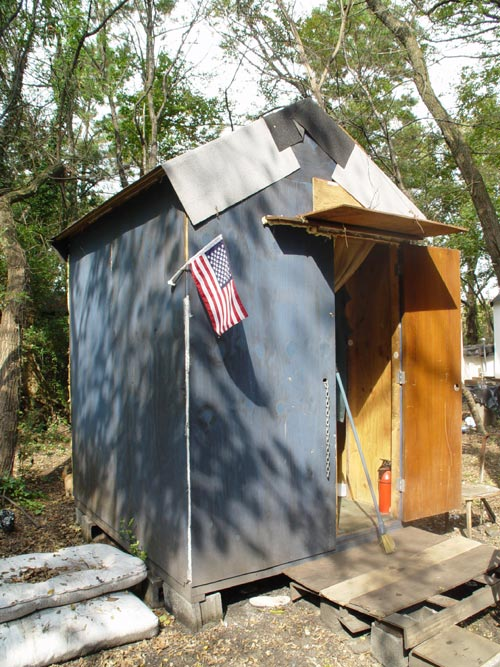 Mad Housers hut. Designer and manufacturer: Mad Housers. United States, 1987. Wood, plywood, nails, roll roofing, plastic and/or screen for windows, silver sheet insulation, paint, caulk, metal flashing, stove pipe and cinderblocks 10 ft x 6 ft x 8  ft. Photo © 2005 Salma Abdulrahman