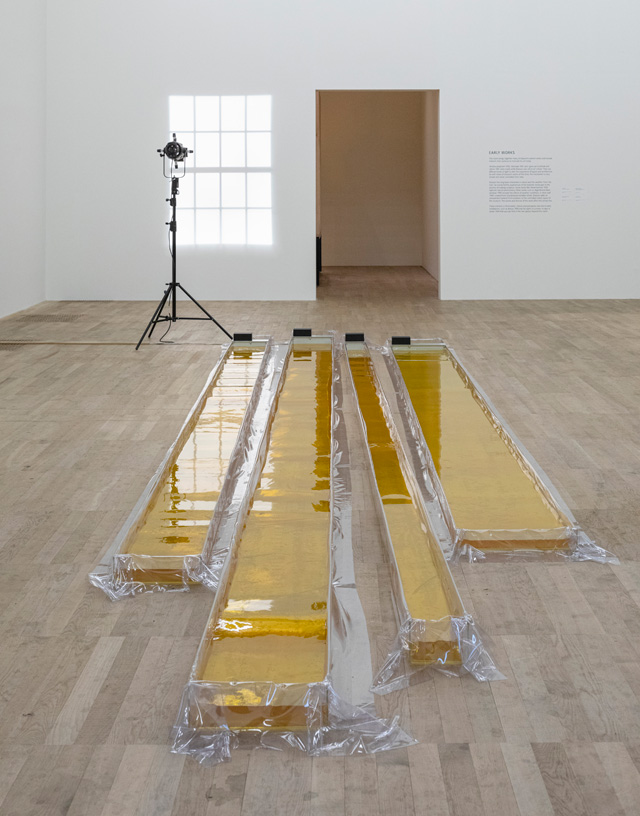 Olafur Eliasson. Wavemachines, 1995. Acrylic, transparent plastic sheet, water, ink (yellow), motors, transformer, 25 x 900 x 212 cm. Installation view, Tate Modern, London, 2019. Photo: Anders Sune Berg. Kunstmuseum Basel. © 1995 Olafur Eliasson.