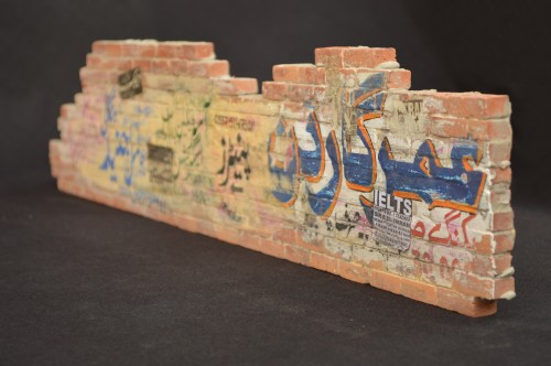 Noor Ali Chagani. The Wall 2, 2014. Terracotta bricks, cement and watercolour, 5 x 23.5 x 0.5 in (12.7 x 59.7 x 1.3 cm). Courtesy of the artist and White Turban Art Consultancy.
