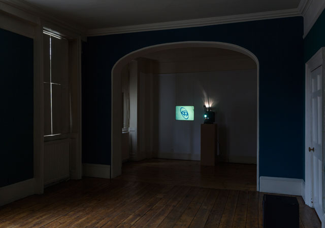 Louisa Fairclough, A Rose, 2017, 1 x 16mm film looped (colour, silent, 9 minutes) projected onto a suspended acrylic screen, 1 x performance for a field recording pressed onto dubplate vinyl (20 minutes). Installation view: A Song cycle for the Ruins of a Psychiatric Unit, Danielle Arnaud Gallery, 2017. Photograph by Oskar Proctor. Courtesy the artist and Danielle Arnaud.