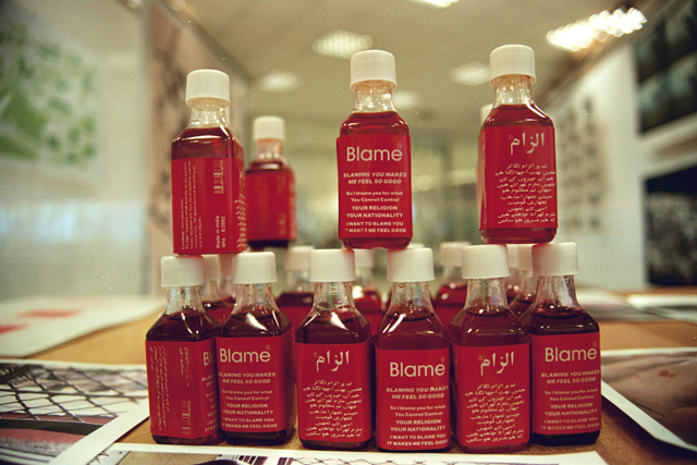 Shilpa Gupta. Blame, 2002–04. Interactive installation with Blame bottles that contain simulated blood, posters, stickers, video, interactive performance, 1 min 49 sec loop. Installation 300 x 130 x 340 cm (118 x 51 x 134 in).