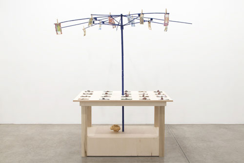 Meschac Gaba. Bureau d'échange [Exchange Office]: Cotton, 2014. Wood table, metal umbrella frame, assorted banknotes, clothespins, cotton stocks, overall; 84 x 80 x 80 in 213 x 203 x 203 cm.