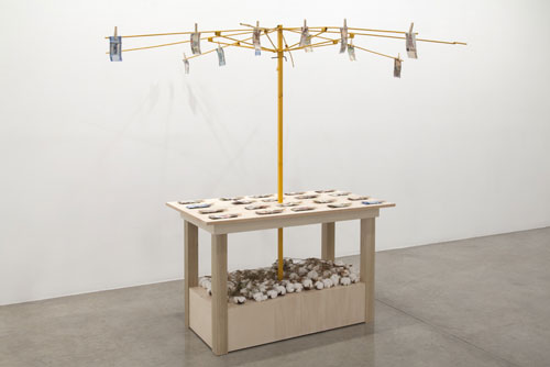 Meschac Gaba. Bureau d'échange [Exchange Office]: Brain, Stone, 2014. Wood table, metal umbrella frame, assorted banknotes, clothespins, electroplated gold brain, rocks and brick pieces, overall; 84 x 80 x 80 in 213 x 203 x 203 cm.