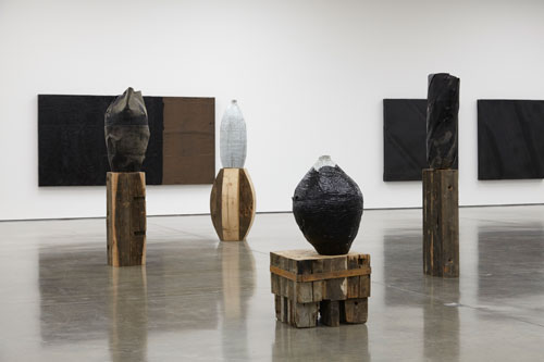 Theaster Gates. Tarred vessel, 2015. Cotton, metal, glazed clay, plastic and tar; Vessel: 31 1/8 x Ø 20 1/16 in (79 x Ø 51 cm); Pedestal: 21 x 24 x 23 1/4 in (53.3 x 61 x 59 cm). © Theaster Gates. Photograph © White Cube (George Darrell).