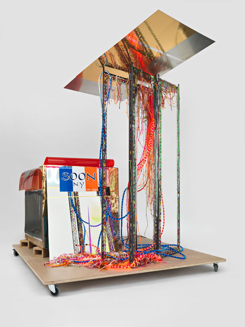 Isa Genzken. Disco Soon (Ground Zero), 2008. Synthetic polymer paint on plastic, cardboard, mirror, spray paint, metal, fabric, hose lights, mirror foil, printed sticker, wood blocks, fiberboard, and casters, 219 x 205 x 165 cm. Carlos and Rosa de la Cruz Collection. Courtesy the artist and Galerie Buchholz, Cologne/Berlin. © Isa Genzken