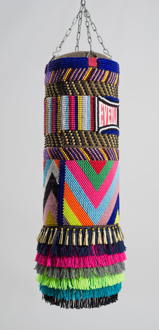 Jeffrey Gibson. This Is Our House, 2014. Found vinyl punching bag, glass and plastic beads, artificial sinew, brass and steel studs, wool military blanket, acrylic yarn, steel chain, 42 x 14 x 14 in. Image courtesy of Jeffrey Gibson Studio. Photograph: Peter Mauney.
