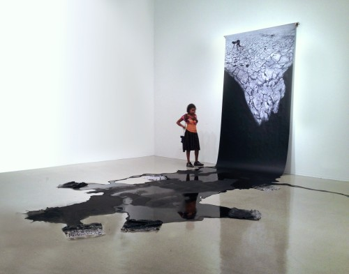 Mwangi Hutter. Aesthetic of Uprising II, 2011. Installation view, Pitzer Art Galleries, Claremont CA. Print on roll, black paint, cleaning rags with text, dimensions variable. Courtesy of the artist.