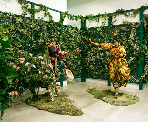 Yinka Shonibare MBE. <em>The        Pursuit</em>, 2007. Two life-sized mannequins, Dutch waxed printed cotton, shoes, coir matting, artificial silk flowers, mixed media, male