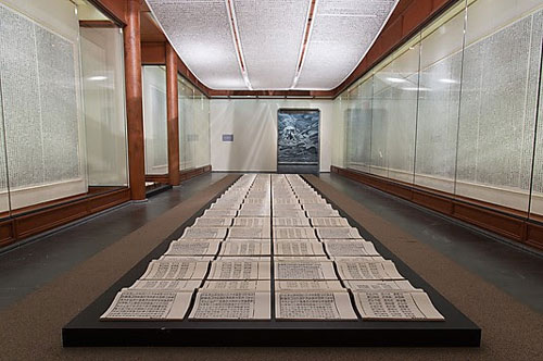 Xu Bing. Book of the Sky, c 1987–91. Installation of hand-printed books and ceiling and wall scrolls printed from wood letterpress type; ink on paper, each book, open: 18 1/8 × 20 in. (46 × 51 cm); three ceiling scrolls, each: 38 in. × approx. 114 ft. 9 7/8 in. (96.5 × 3500 cm); each wall scroll: 9 ft. 2 1/4 in. × 39 3/8 in. (280 × 100 cm). Lent by the artist. © Xu Bing.