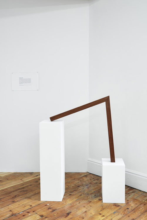 Iman Issa. Surrealism III (study for 2014). Mahogany sculpture, text panel under glass and two white plinths. Sculpture 79.6 x 75 x 5 cm; small plinth 45 x 25 x 25 cm; large plinth 93.3 x 25 x 25 cm, 2014.