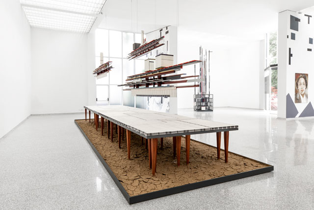 Remy Jungerman. Visiting Deities, 2018-19. Cotton textile, kaolin, dry river clay, water samples, painted wood, 58 table legs (meranti), yarn, mirror and nails, 384 x 138 x 102 in (975 x 350 x 260 cm). Photo: Aatjan Renders.