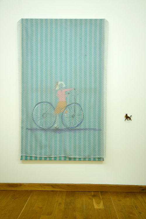 Jenny Watson. <em>Bicycle girl</em> 2007. Acrylic on rabbit skin glue primed cotton, stretched, with flecked voile overlay + s mall plastic horse, 152 cm x 89 cm.  Courtesy Transit Gallery, Mechelen, Belgium.